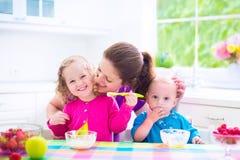 Moder och ungar som har frukosten Royaltyfri Foto
