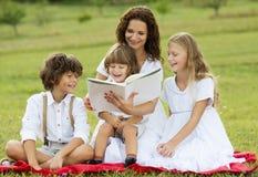 Moder och ungar som läser en bok Arkivbild