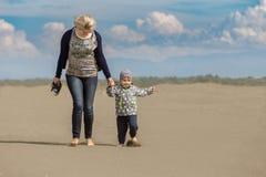 Moder och unge på stranden Royaltyfria Foton