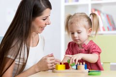 Moder och unge som hemma spelar logiska leksaker Royaltyfri Fotografi