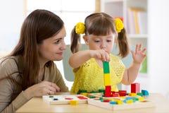 Moder och unge som hemma spelar logiska leksaker Royaltyfri Foto