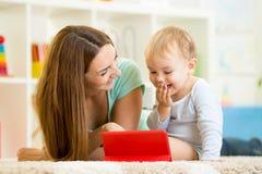 Moder- och ungelek på minnestavladatoren Arkivbild