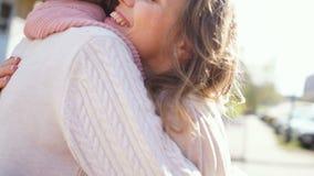 Moder och vuxen dotter att krama sig p? gatan i soligt, bl?sv?der Tr?d blommar omkring arkivfilmer