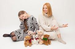Moder- och vuxen människadotter på vit bakgrund med mjuka leksaker Fotografering för Bildbyråer
