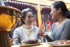 Moder- och vuxen människadotter som tycker om mål för traditionell kines arkivbild