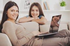 Moder som använder bärbara datorn, medan sitta på soffan royaltyfria bilder