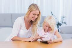 Moder som använder den digitala minnestavlan med hennes dotter Royaltyfri Foto