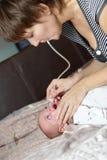 Moder som använder den nasala aspiratoren Arkivbilder