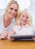 Moder som använder minnestavlaPC med hennes dotter Royaltyfri Foto