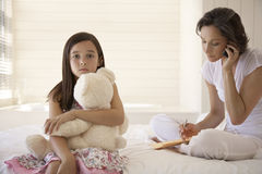 Moder som använder mobiltelefonen med dottern som rymmer Teddy Sitting On Bed Royaltyfri Bild