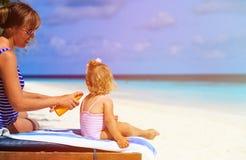 Moder som applicerar sunblockkräm på dotterskuldra Fotografering för Bildbyråer