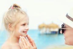 Moder som applicerar sunscreenskyddskräm på gullig liten litet barnpojkeframsida Mamma som använder sunblocking lotion för att sk arkivbilder