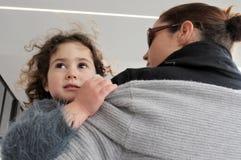 Moder som att bry sig hennes dotter på hennes armar i stadsgata royaltyfria foton