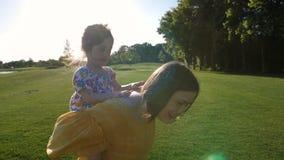 Moder som bär den förtjusande lyckliga dottern på baksida lager videofilmer