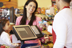 Moder som betalar för familjshopping på kontrollen med kortet Arkivbild