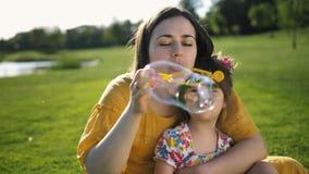 Moder som blåser såpbubblor med den speciala dottern
