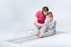 Moder som blidkar den skriande dottern under utbildning Fotografering för Bildbyråer