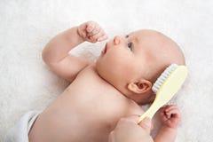 Moder som borstar Newborn& x27; s-hår Royaltyfri Fotografi