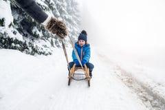 moder som drar pulkasonen Dimmig vit vinternatur royaltyfria foton