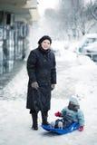 Moder som drar ungen på pulkan Arkivfoto