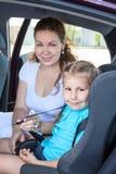 Moder som fäster den lilla dottern in i den begynnande säkerhetsplatsbilen Royaltyfri Foto