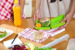 Moder som förbereder den sunda lunchasken för barn Royaltyfri Fotografi