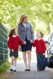 Moder som går till skolan med barn på väg att arbeta Arkivbilder