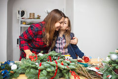 Moder som gör en adventkrans med dottern Royaltyfri Fotografi