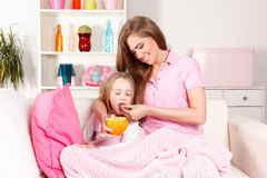 Moder som ger frukt till det sjuka barnet arkivbild