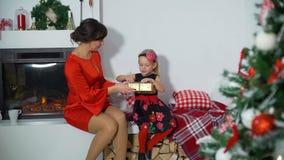 Moder som ger julklapp till hennes dotter arkivfilmer