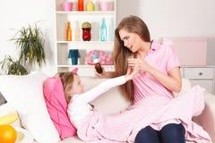 Moder som ger medicin till barnet royaltyfri bild