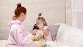 Moder som häller antipyretic sirap till det sjuka lilla barnet lager videofilmer