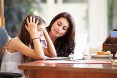 Moder som hjälper den stressade tonårs- dottern som ser bärbara datorn Arkivfoton
