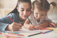 Moder som hjälper hennes liten flicka till att skriva hemma royaltyfri bild
