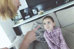 Moder som inomhus grälar på det upprivna nätta barnet arkivbild
