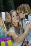 Moder som klickar självfotoet medan kyssa för ungar Arkivbild