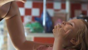 Moder som kontrollerar tänder av flickan stock video