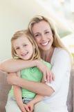 Moder som kramar henne dotter på soffan Royaltyfria Bilder