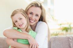 Moder som kramar henne dotter på sofaen Royaltyfri Foto