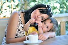 Moder som kramar sonen Arkivbild