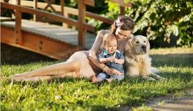 Moder som kramar sonen och husdjuret Arkivbilder