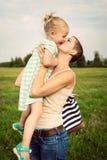 Moder som kysser den förtjusande le dottern arkivfoto
