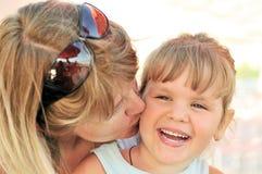 Moder som kysser henne liten dotter Arkivbild