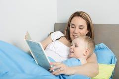 Moder som läser en berättelse till hennes son arkivfoton