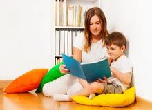 Moder som läser en berättelse till hennes ungeson Arkivbilder
