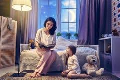 Moder som läser en bok arkivbild