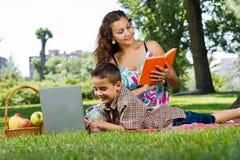 Moder som läser en bok i park Royaltyfri Bild