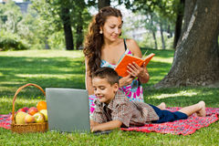 Moder som läser en bok i park Arkivbilder
