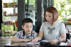 Moder som läser en bok med hennes son arkivfoton