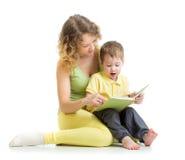 Moder som läser en bok till barnpojken Arkivfoto